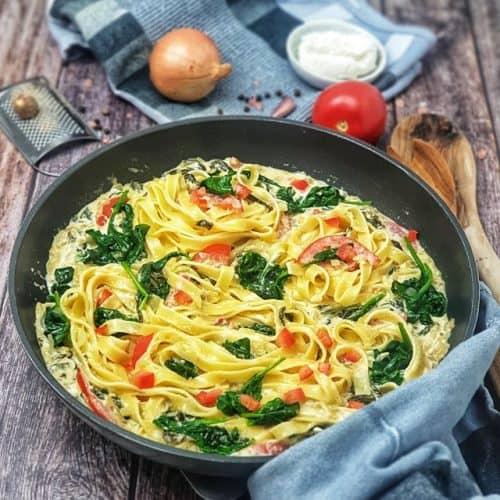 Eine vegetarisdche Nudelpfanne mit Ricotta, Spinat und Tomaten, angerichtet und dekorativ fotografiert in der Pfanne. Im Hintergrund auf einem Küchenhandtuch Tomate, Zwiebel und ein Schälchen Ricotta. Neben der Pfanne liegt ein Holzlöffel.