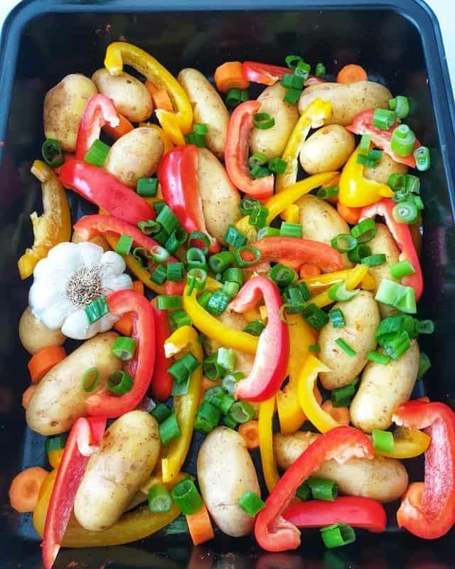 Vorbereitung für Hähnchen mit Kartoffel-Gemüse: Die Kartoffeln gründlich waschen, größere Kartoffeln halbieren. Die Paprikaschoten waschen, putzen und in Scheiben schneiden. Den Lauch waschen und in Ringe schneiden. Die Möhren schälen und in Ringe schneiden. Die Kartoffeln und das Gemüse in einer großen Auflaufform verteilen.