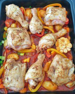 Auf dem Gemüse und der Tomatensoße liegen die angebratenen Hähnchenteile.