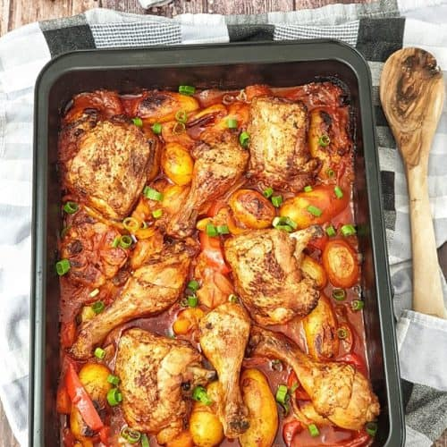 Das Hähnchen mit Kartoffel-Gemüse nach dem Backen im Ofen mit Frühlingszwiebeln bestreut und dekorativ fotografiert. Im Hintergrund auf einem Küchenhandtuch eine Kartoffel, eine Zwiebel und eine Möhre. Neben der Auflaufform ein Holzlöffel.