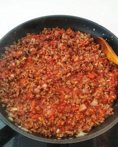 In einer Pfanne angebratenes Hackfleisch mit gehackten Tomaten.