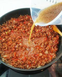 In einer Pfanne angebratenes Hackfleisch mit gehackten Tomaten und Brühe.