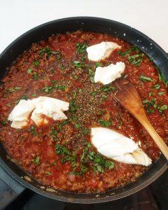 In einer Pfanne Tomatensoße mit Hackfleisch und Creme Fraiche.