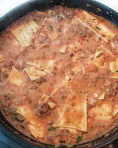 In einer Pfanne Lasagne Platten in Tomaten Soße.