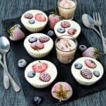 Auf einer Schieferplatte angerichtet Frozen Yoghurt Muffins mit Früchten.