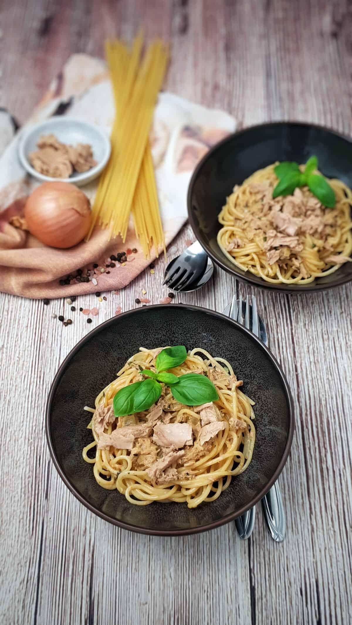 In einer braunen Schale angerichtet Spaghetti mit einer Thunfisch-Sahne-Soße. Im Hintergrund Deko.
