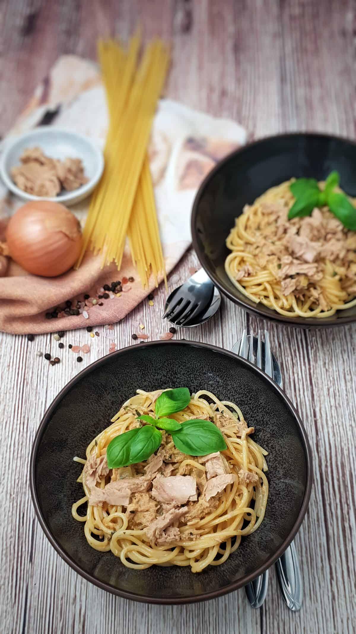 In einer braunen Schale angerichtet Spaghetti mit einer Thunfisch Soße. Im Hintergrund Deko.