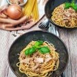 Spaghetti mit Thunfisch-Sahne Soße werden mit frischem Basilikum bestreut serviert