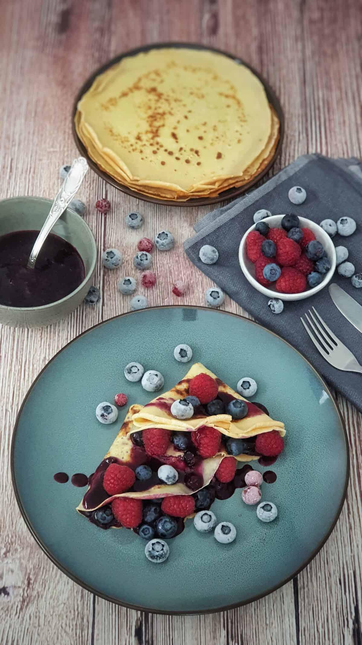 Auf einem blauen Teller ein Crêpes gefüllt mit Früchten und Heidelbeer Kompott.