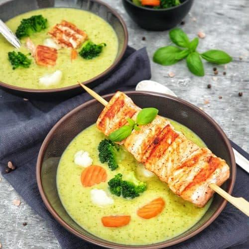 Brokkoli Creme Suppe mit einem Lachsspieß in einer braunen Schale serviert. Der Lachsspieß ist angebraten und auf dem Schälchen drapiert.