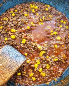 In einer Pfanne Chili mit Hackfleisch und Mais.