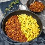 In einer Pfanne Chili con Carne neben angebratenen Spätzle angerichtet,