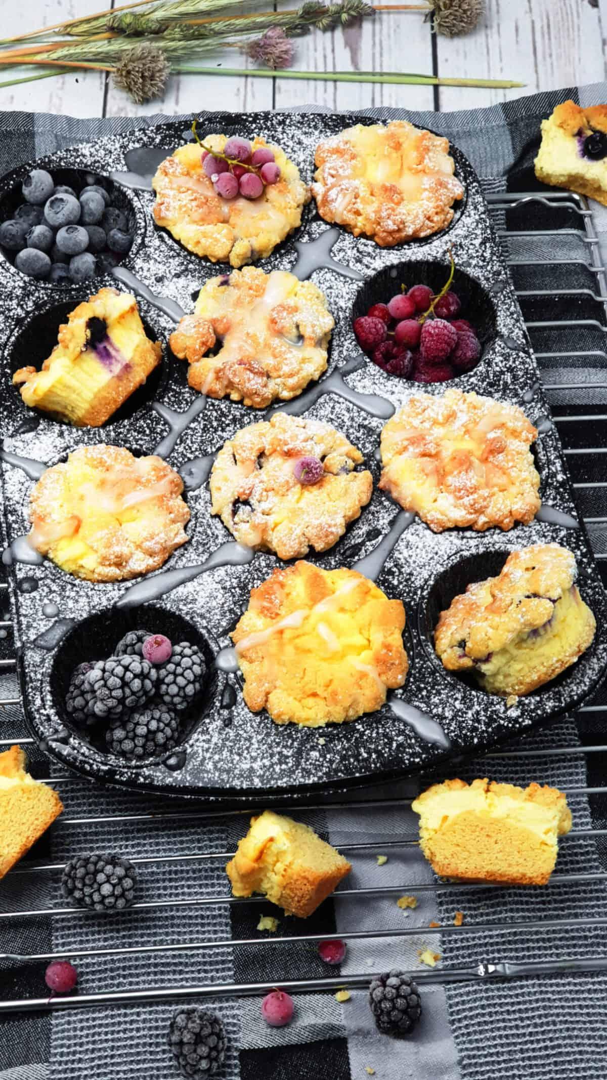 In einer Muffinform Cheesecake Muffins mit Heidelbeeren. Dekorativ angerichtet und fotografiert. Im Hintergrund Deko.