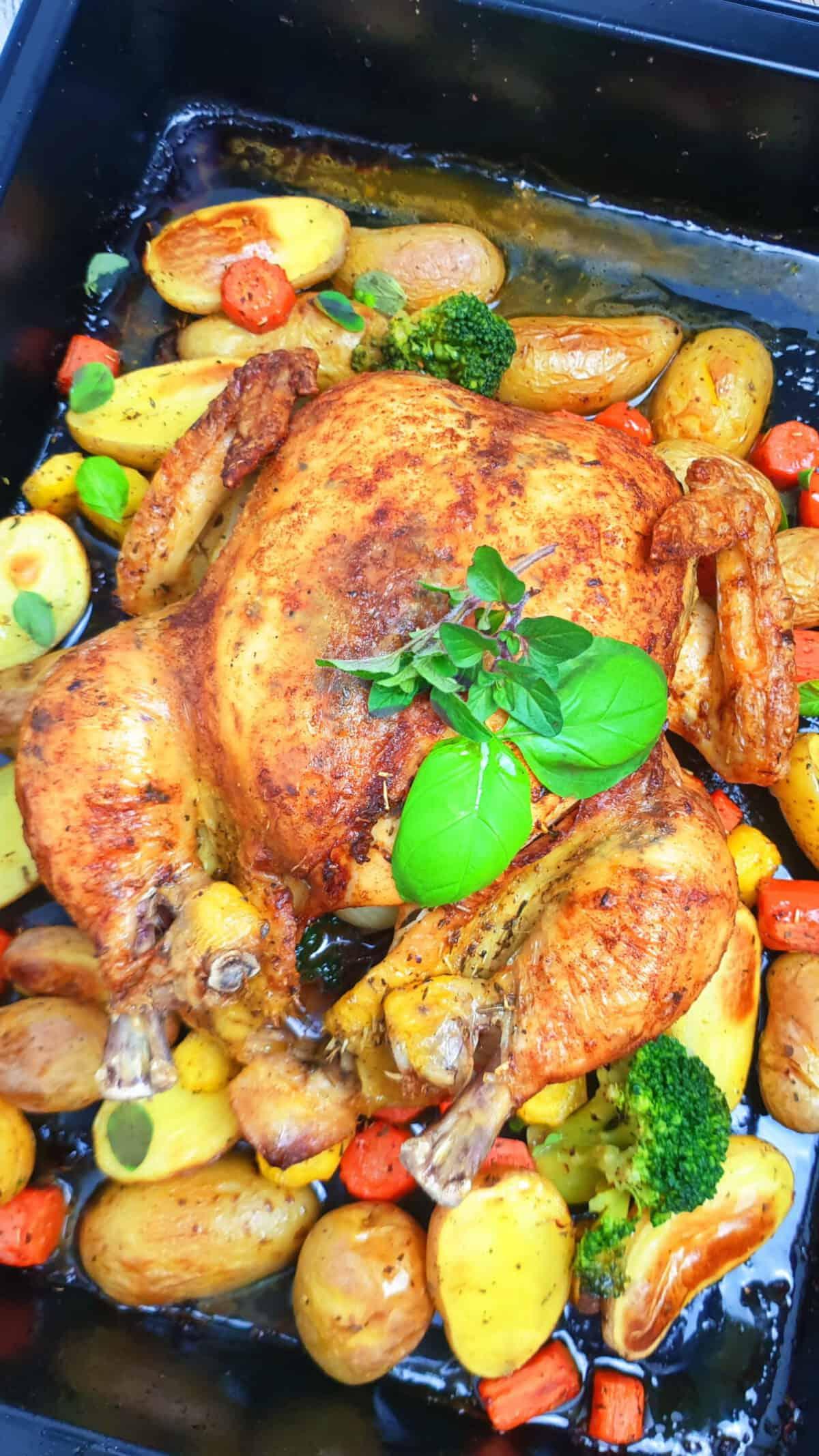 Ein ganzes Hähnchen / Poularde im Backofen gebacken mit Kartoffeln und Gemüse auf einem Backblech.