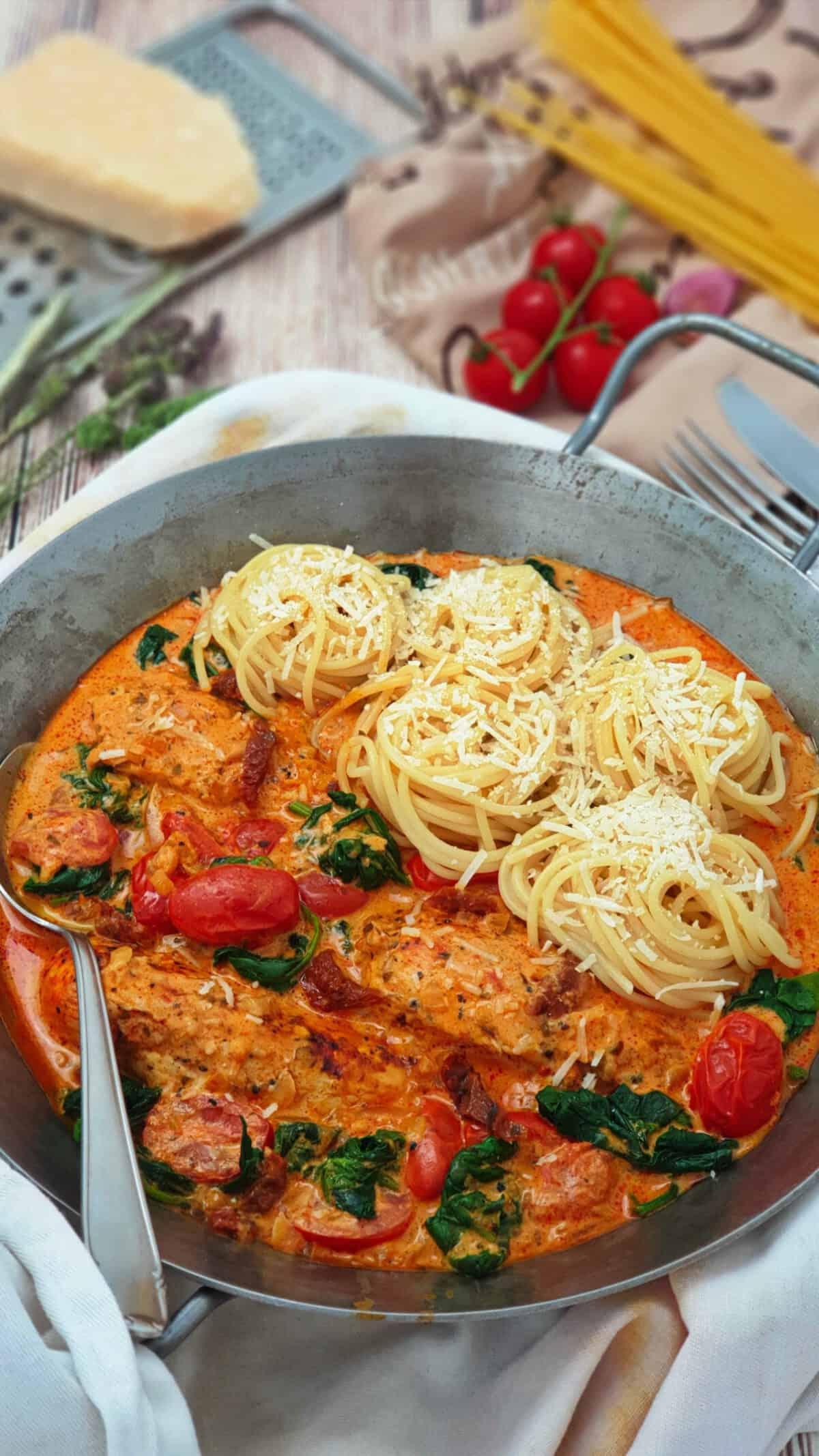 In einer eisernen Pfanne Hähnchenfilet in cremiger Frischkäse-Parmesan-Soße mit Spaghetti Nestern.
