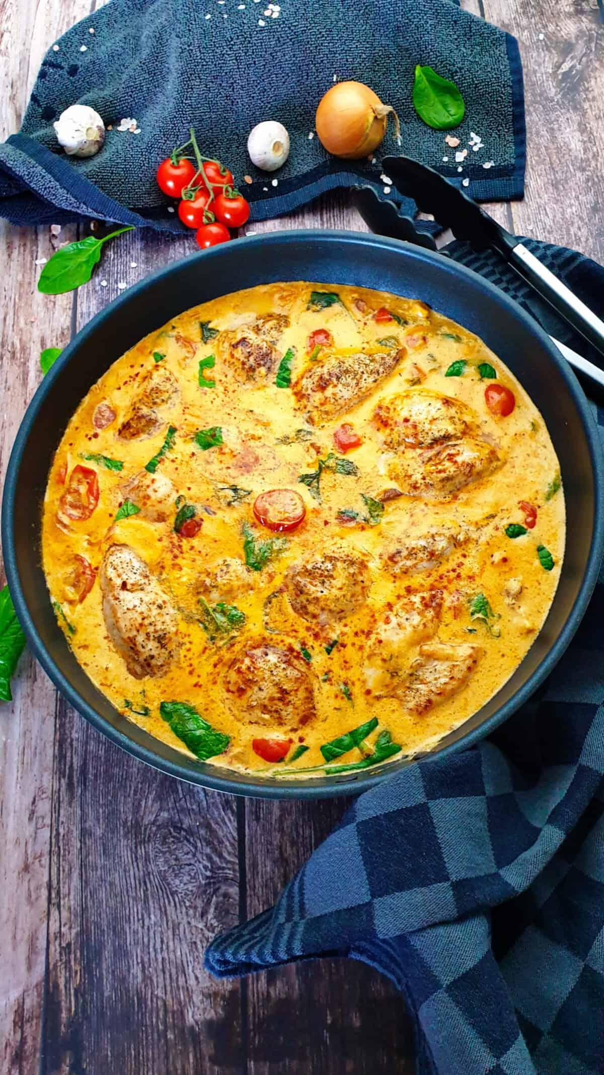 In einer Pfanne angerichtet Hähnchenfilet in einer Frischkäse-Parmesan-Soße mit Petersilie bestreut.