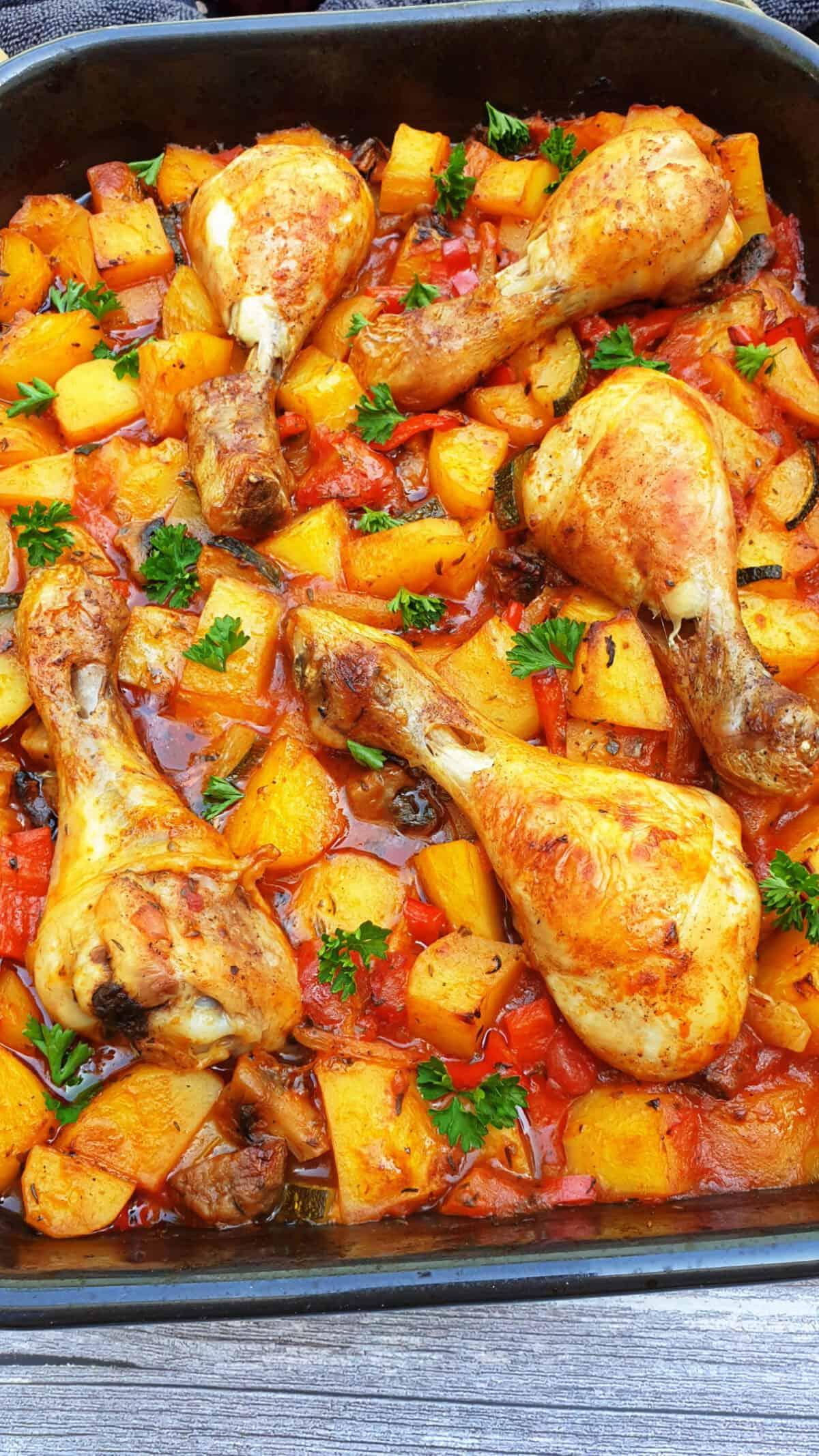 In einer dunklen Auflaufform Hähnchenunterkeulen mit Kartoffeln und Tomatensoße.