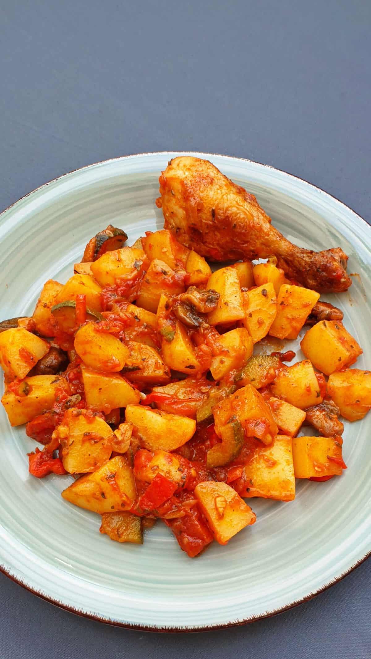 Auf einem grünen Teller eine Hähnchenunterkeule mit Kartoffel-Gemüse und Tomatensoße.