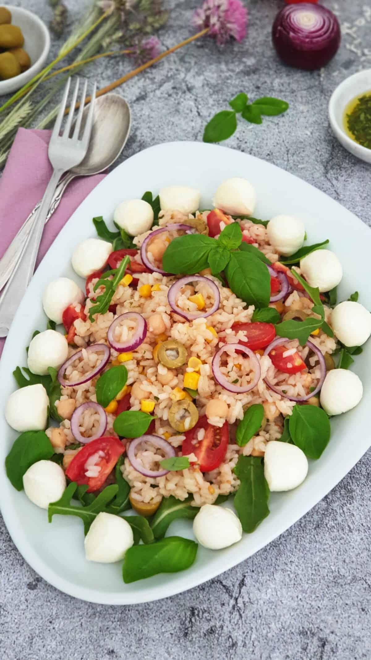 Auf einer weißen Platte angerichtet ein Italienischer Reis-Salat mit Mozzarella und Rucola. Im Hintergrund Deko.