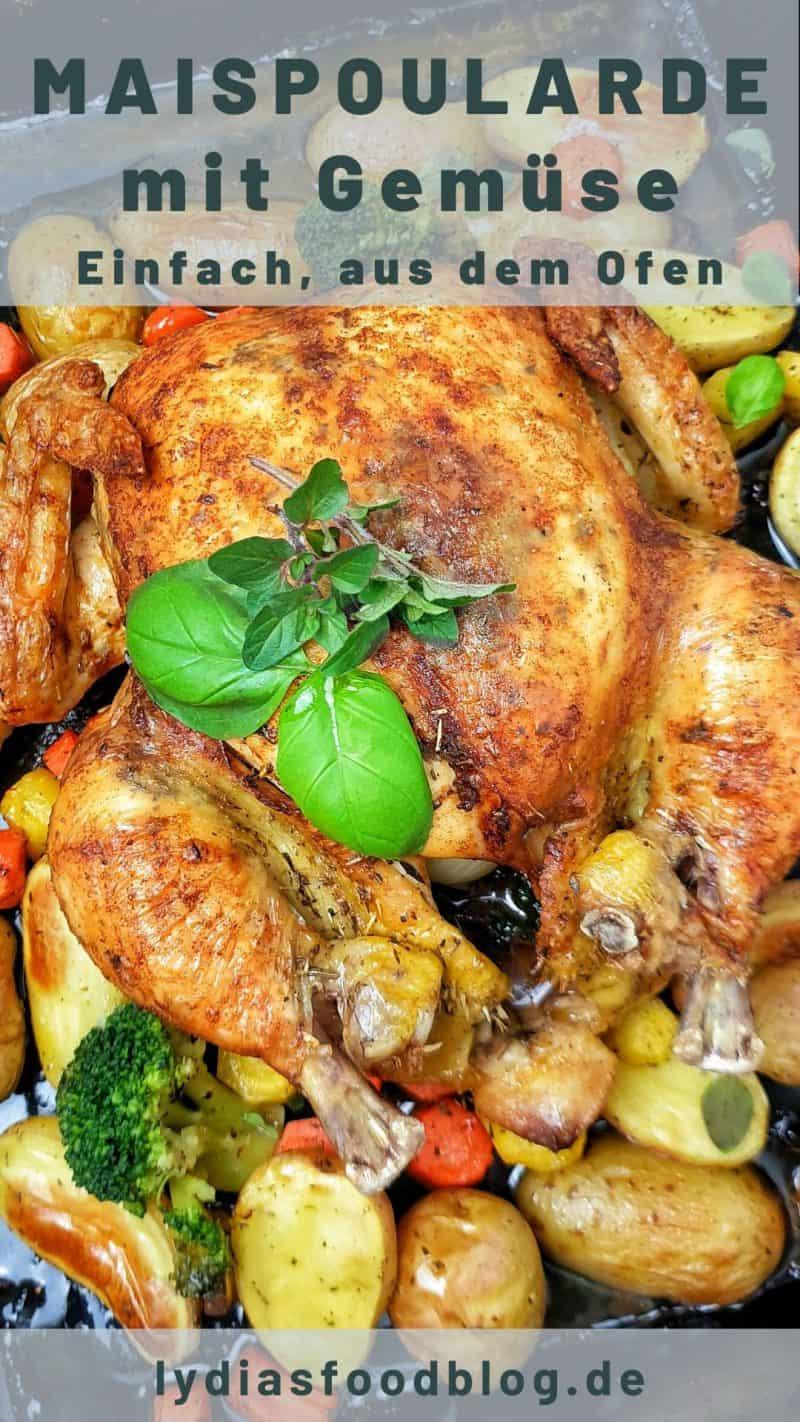 Auf einem Backblech eine Maispoularde im Ganzem gegart mit Kartoffel-Möhren-Gemüse. Dekoriert mit frischer Petersilie und Basilikum.