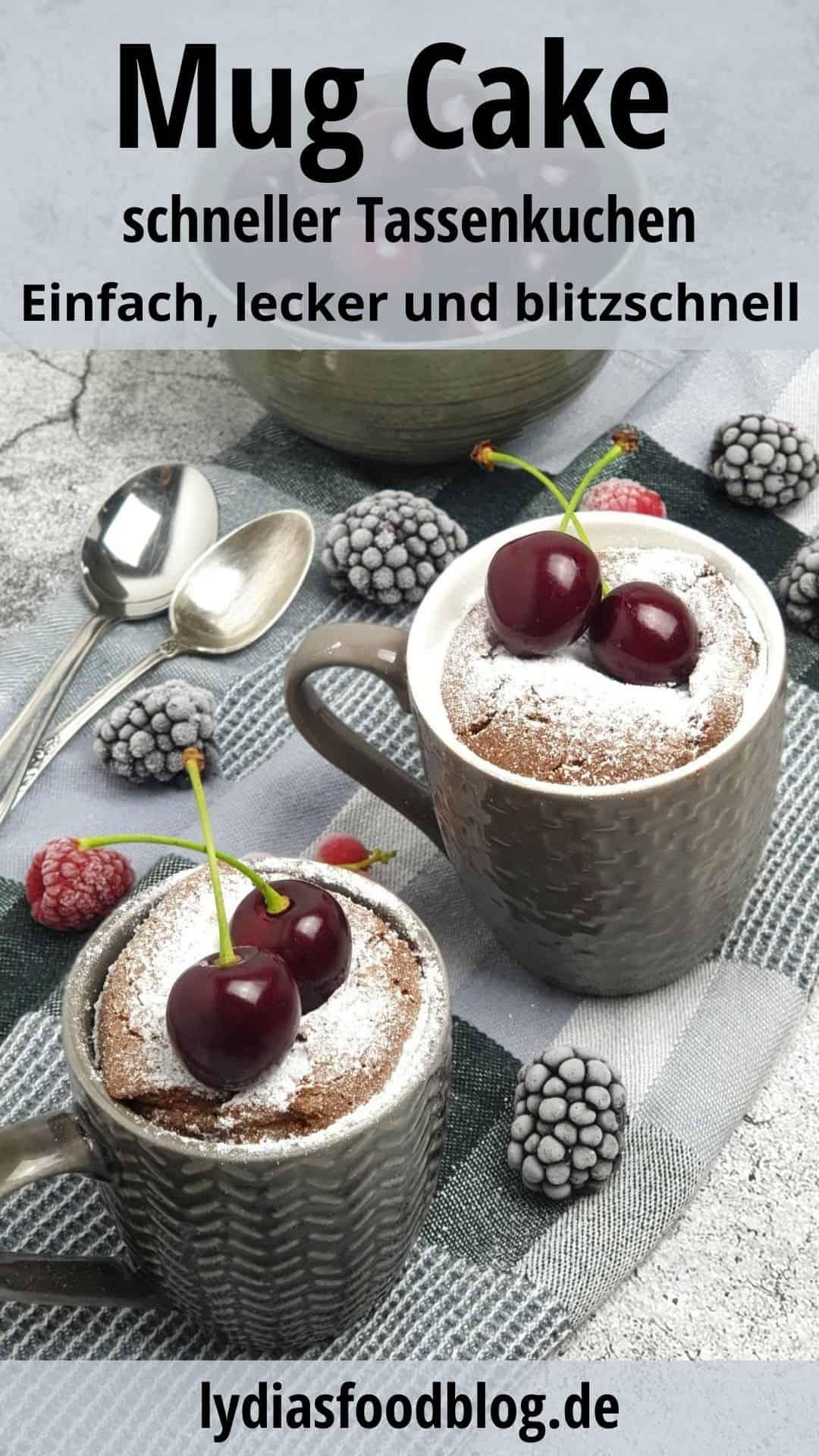 Zwei graue Tassen mit einem Mug Cake - Tassenkuchen. Bestreut mit Puderzucker und garniert mit Kirschen.