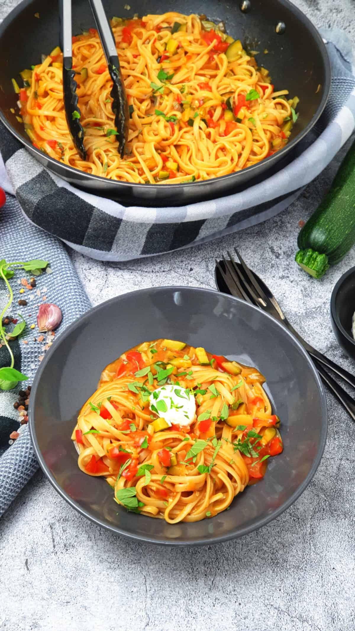 In einer grauen Schale One Pot Pasta mit Paprika und Zucchini. Im Hintergrund eine Pfanne und Deko.