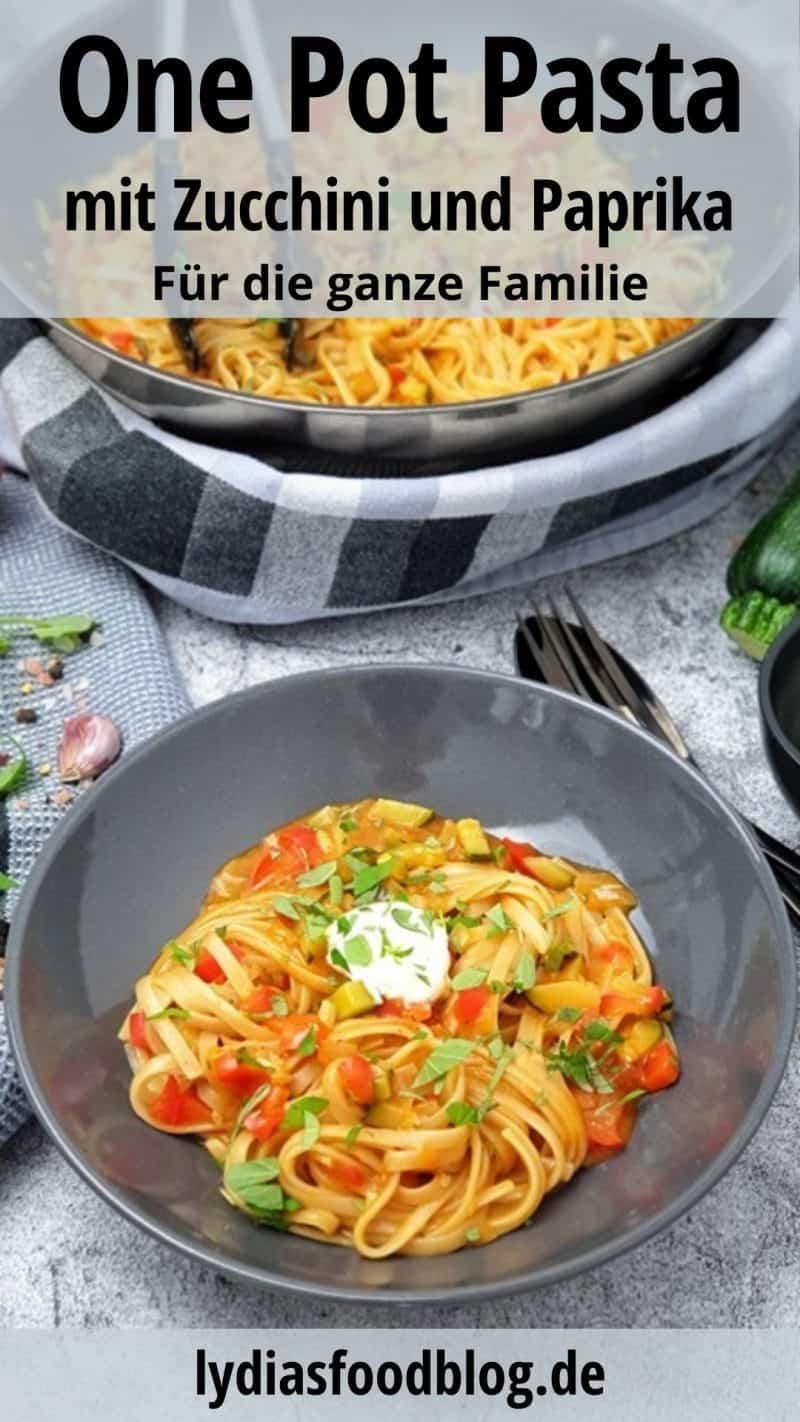 In einer grauen Schale angerichtet One Pot Pasta mit Paprika und Zucchini. Im Hintergrund eine Wokpfanne. Neben dem Teller liegt schwarzes Besteck.