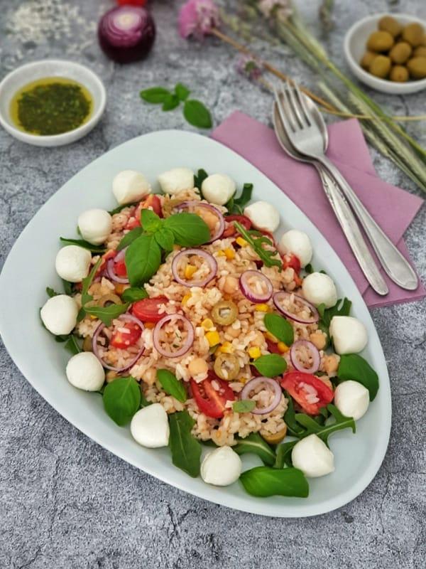 Ein italienischer Reissalat mit Tomaten, Kichererbsen, Oliven und Mozzarella angerichtet auf einem Rucola Beet auf einer weißen Servierplatte. Im Hintergrund Deko.