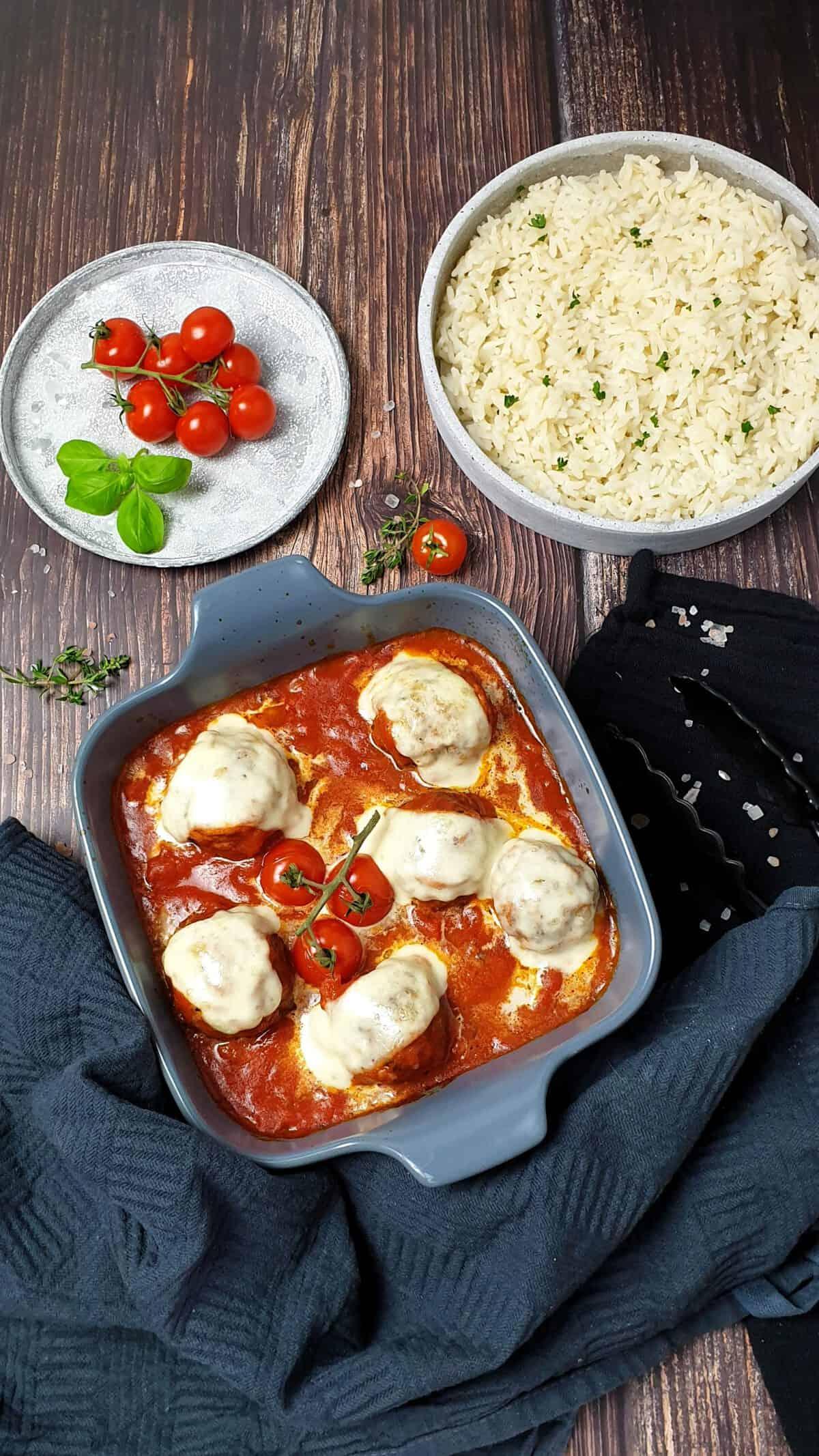 In einer grauen Auflaufform Hackfleischbällchen mit Mozzarella überbacken. Daneben eine Schale mit Reis sowie ein Teller mit Tomaten und Basilikum zur Deko.