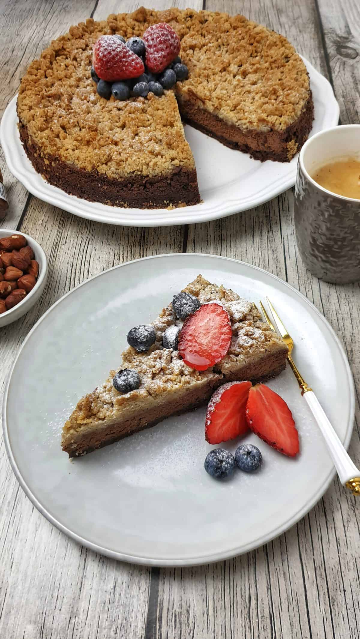 Ein Stück Schoko-Kuchen auf einem hellen Teller mit frischen Beeren garniert. Im Hintergrund Deko.