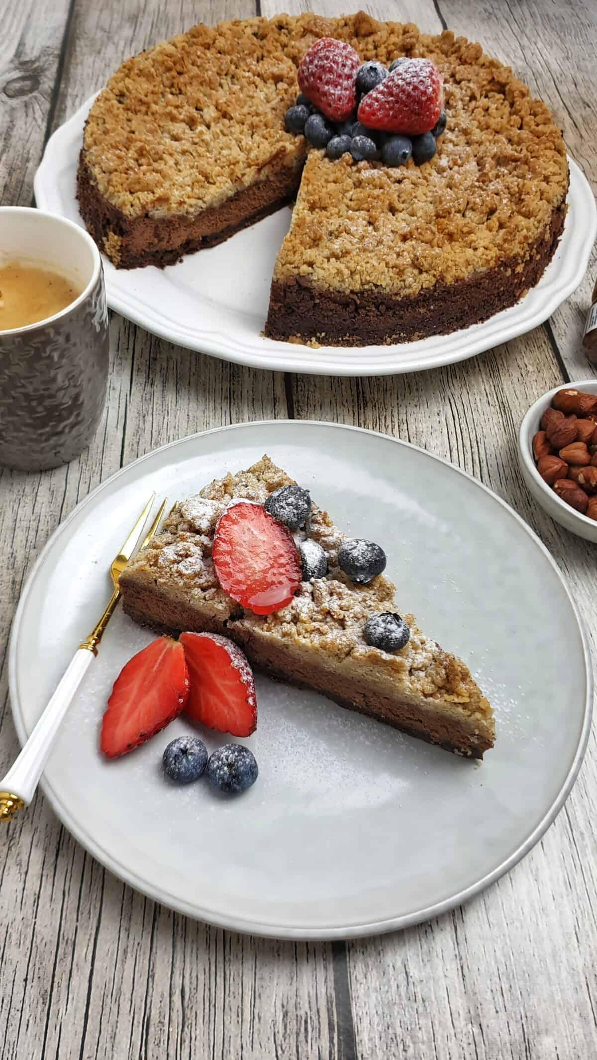 Ein Stück Schokoladen-Kuchen auf einem hellen Teller mit frischen Beeren garniert. Im Hintergrund Deko.