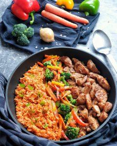 Zartes Hähnchen mit Tomatenreis und Gemüse angerichtet in einer Pfanne. Im Hintergrund auf einem Küchentuch frisches Gemüse dekorativ drapiert.