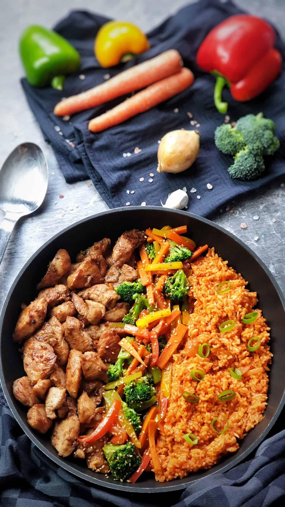 In einer Pfanne nebeneinander angerichtet Tomaten-Reis mir Gemüse und Hähnchen.