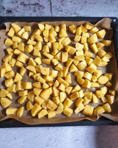 Die Kartoffeln sind in Würfel geschnitten und mit Gewürzen und Öl mariniert auf einem Backblech mit Backpapier zu sehen.