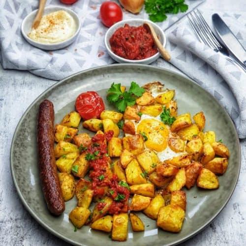 Patatas bravas mit Spiegelei und Merguez Bratwurst, Tomatensoße, Aioli und Merguez Wurst, serviert und angerichtet auf einem grünen Steingut Teller. Im Hintergrund ein Schälchen Tomatensoße und ein Schälchen Aioli auf einem Küchenhandtuch dekorativ angerichtet.