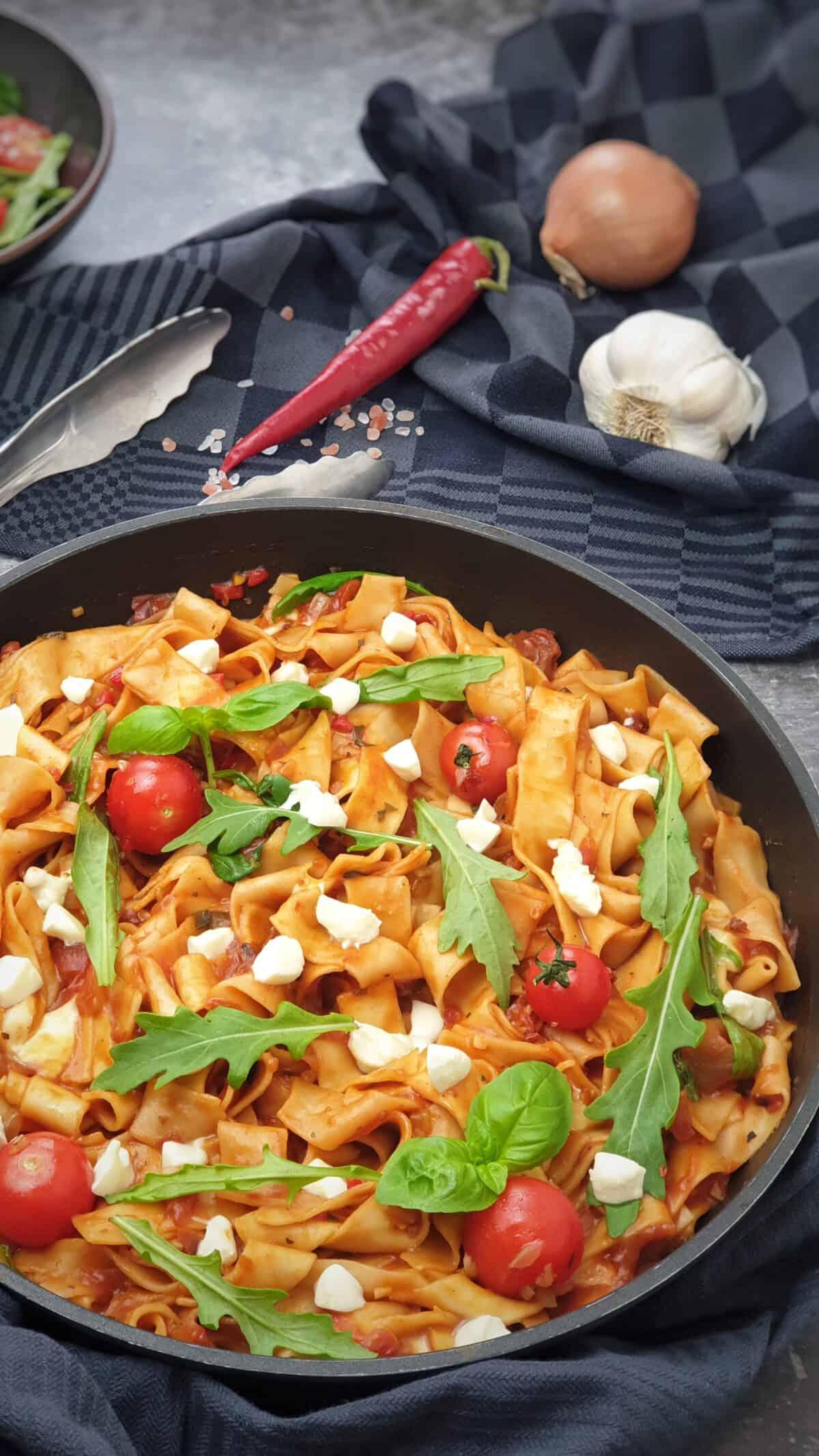 In einer Pfanne angerichtet One Pot Sommer Pasta mit Tomate, Rucola und Mozzarella.