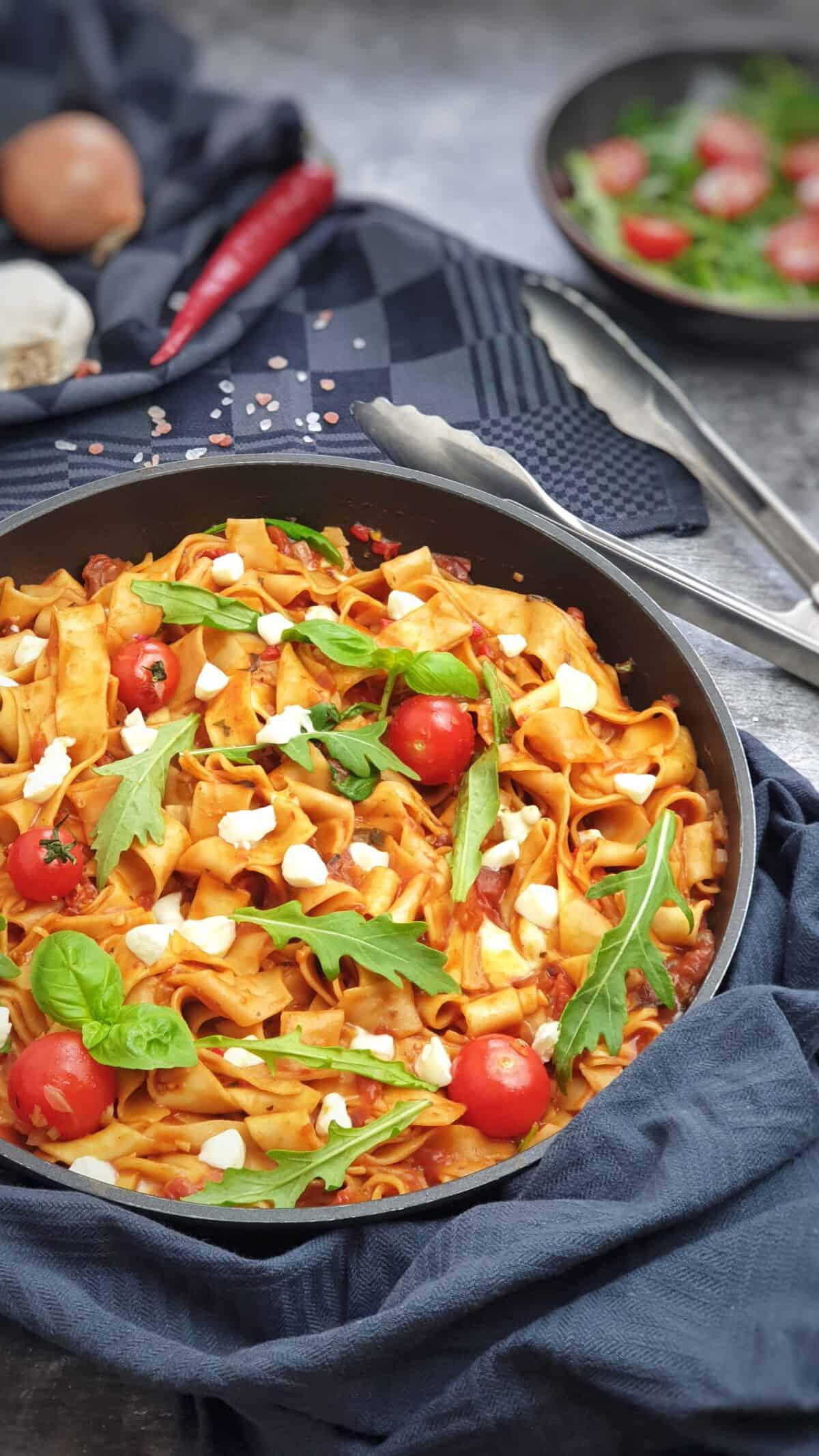 In einer Pfanne angerichtet eine sommerliche One-Pot Pasta mit Tomate, Rucola und Mozarella.