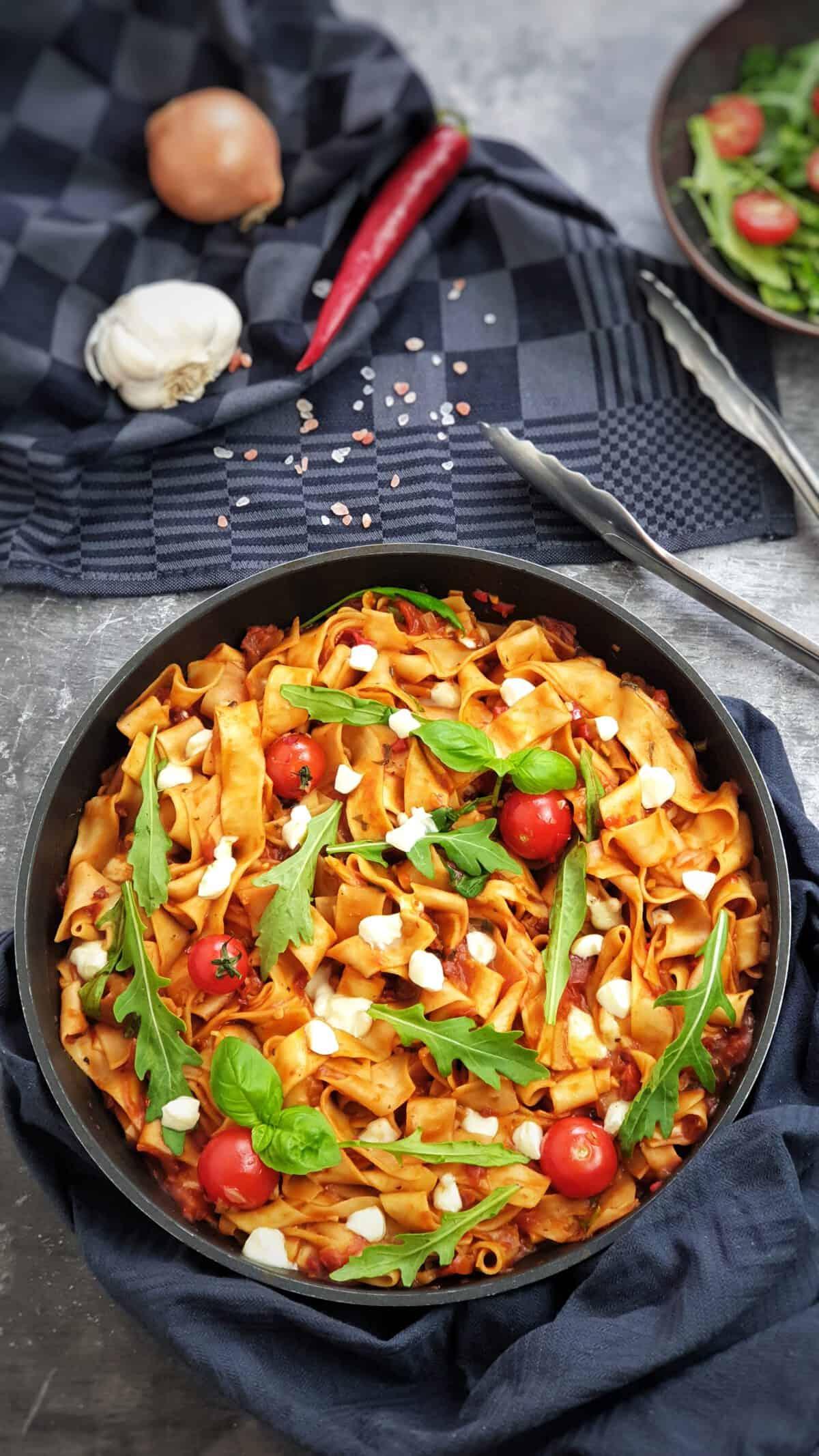 In einer Pfanne angerichtet eine sommerliche One Pot Pasta mit Tomate, Rucola und Mozzarella.