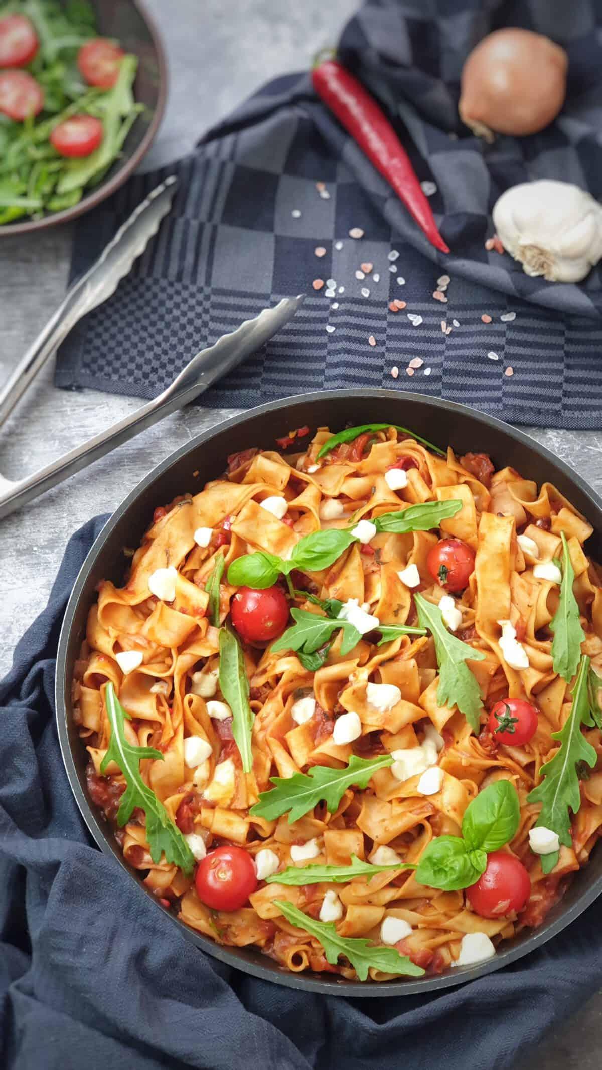 In einer Pfanne angerichtet One-Pot-Sommer-Pasta mit Tomate, Rucola und Mozzarella.