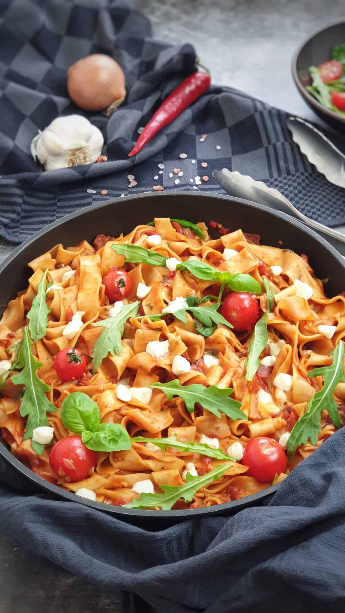 In einer Pfanne angerichtet eine sommerliche One Pot Pasta mit Tomate, Rucola und Mozarella.