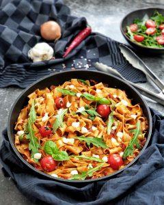 One Pot Pasta mit Peperoni, Rucola und Mozzarella in der Pfanne fotografiert. Im Hintergrund steht eine schale mit frischem Salat. Daneben auf einem Küchenhandtuch liegt eine Zwiebel, eine Knoblauchzehe und eine Peperoni.