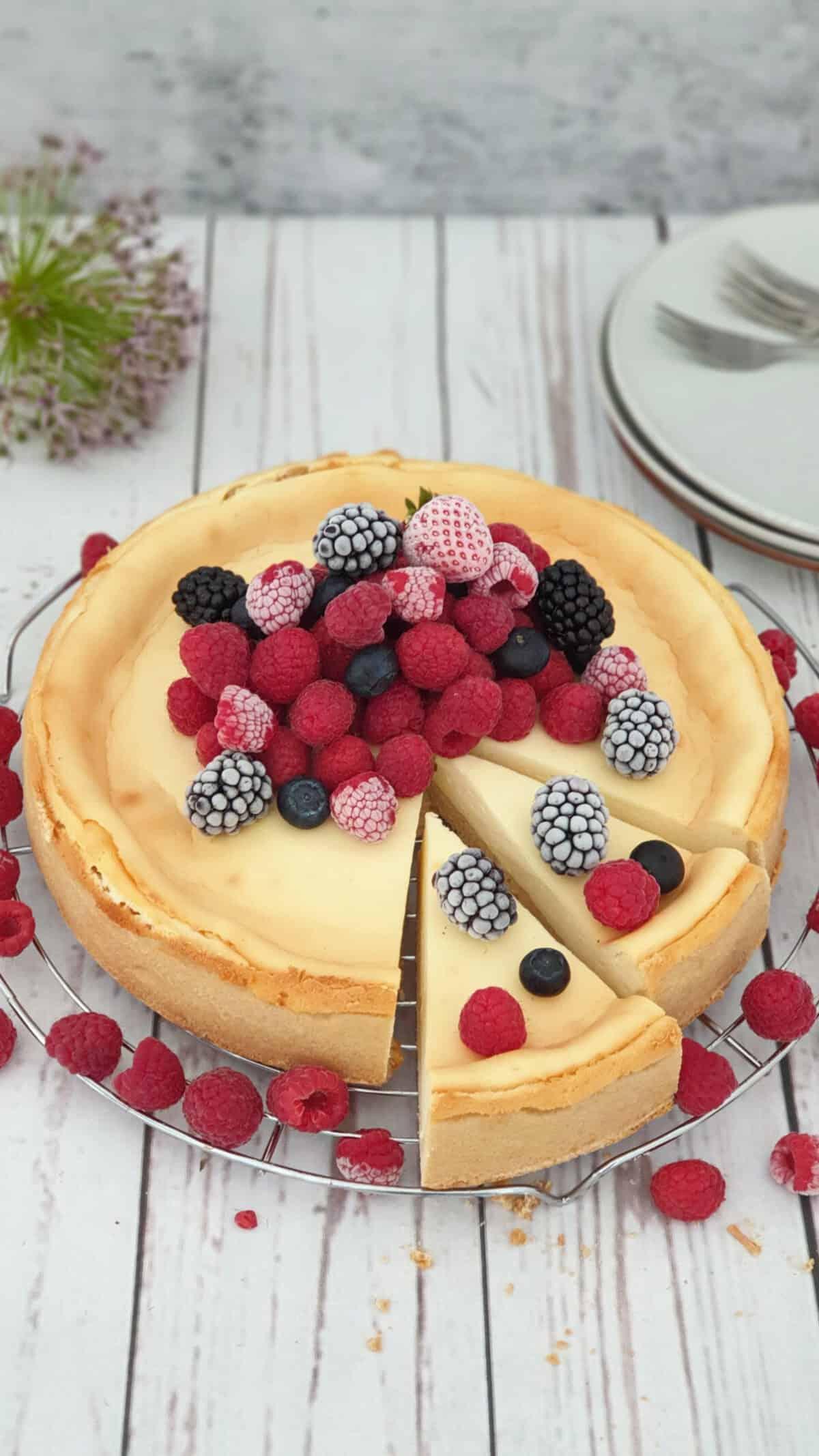 Auf einem Kuchenrost ein Cheesecake mit frischen Beeren und Früchten.. Im Hintergrund Deko.