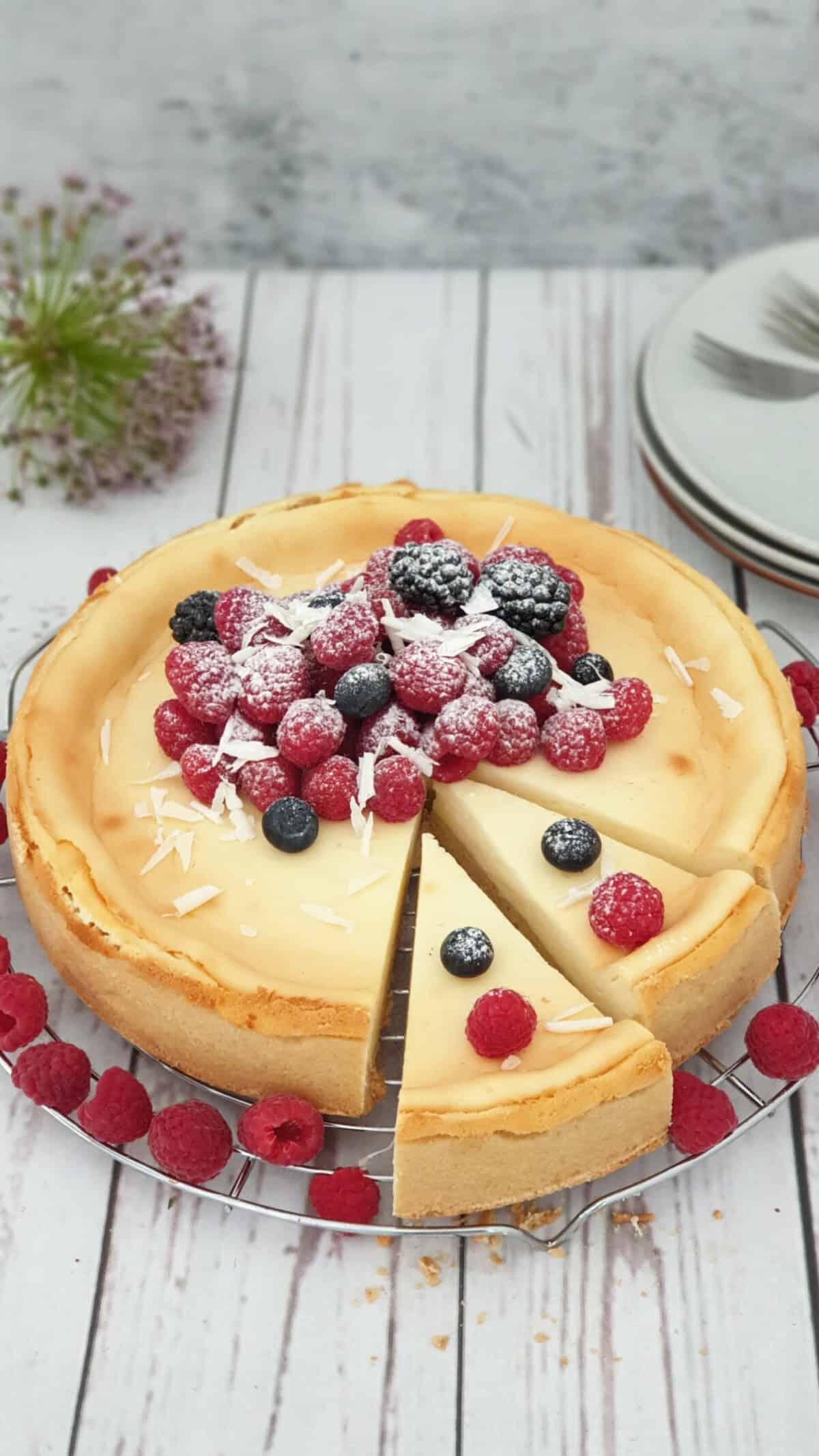 Auf einem Kuchenrost ein Cheesecake mit frischen Beeren und Früchten mit Puderzucker bestreut. Im Hintergrund Deko.