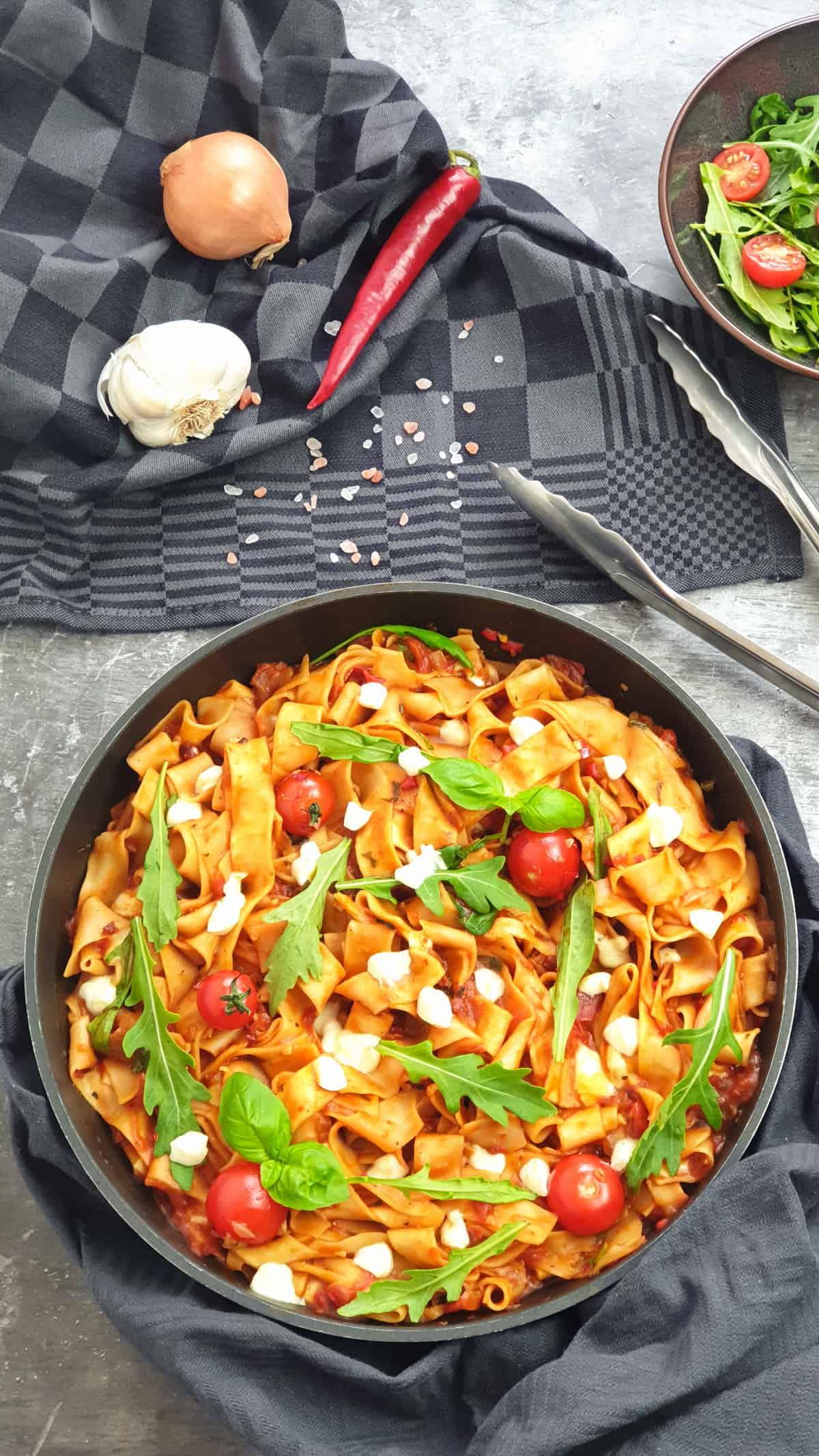 One Pot Pasta mit Bandnudeln, Rucola, Tomaten und Mozzarella in einer Pfanne. Im Hintergrund Deko.