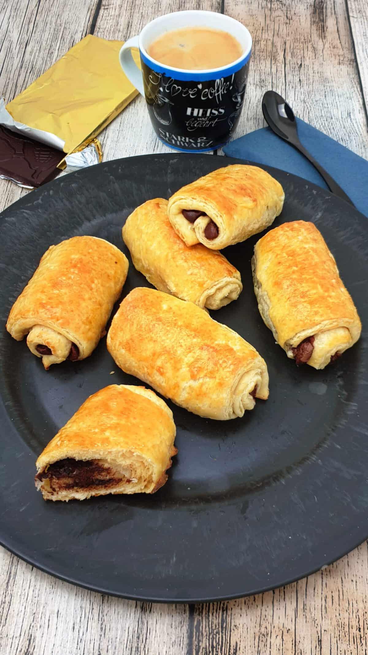 Auf einem grauen Teller drei Schoko-Croissants. Im Hintergrund Deko.