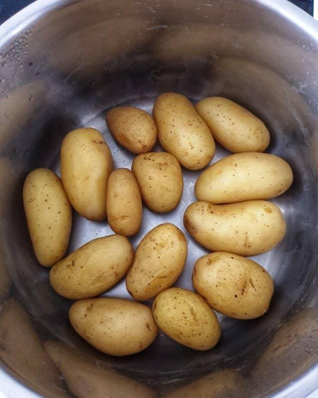 Die Pellkartoffeln für den klassischen Kartoffelsalat in Salzwasser kochen, ab´gießen und auskühlen lassen.