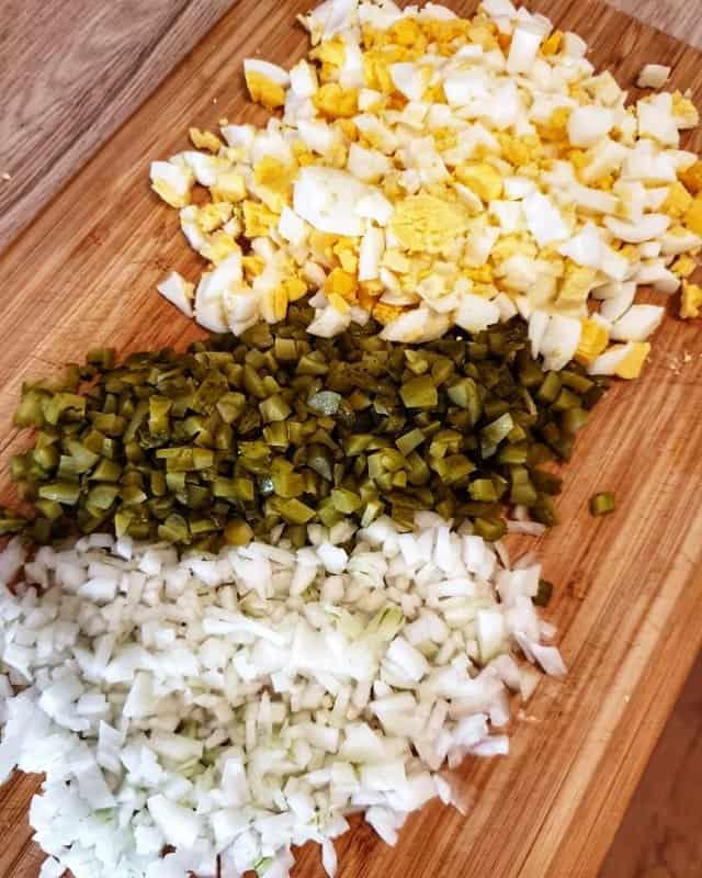 Die Eier für 10 Minuten kochen und danach abpellen und in Würfel schnein. Gewürzgurken und Zwiebeln ebenfalls fein würfeln.