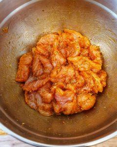 Das Putenfleisch ist in Streifen geschnitten in einer Schale und mit Öl und Gyrosgewürz gewürzt.