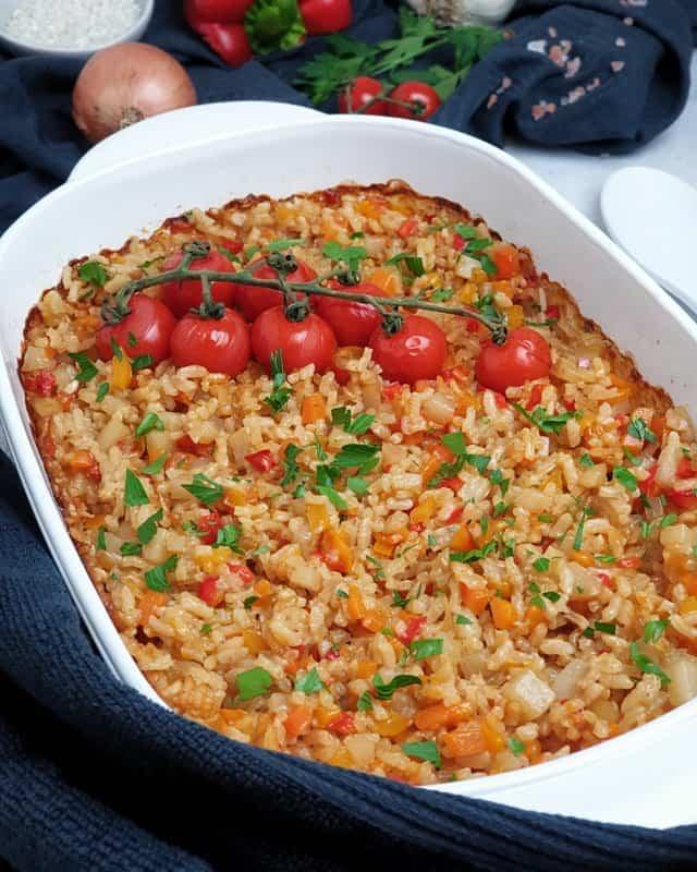 In einer weißen Auflaufform, ein buntes Risotto aus dem Ofen mit Möhren, Kohlrabi und Tomaten.