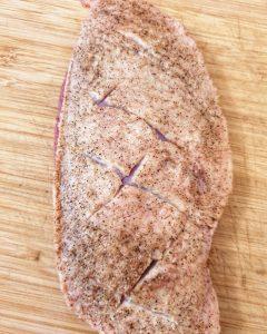 Auf einem Küchenbrett eingeschnittene und gewürzte Entenbrust mit Haut.